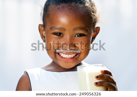 Close up fun portrait of cute African girl showing white milk mustache.Isolated against light background. - stock photo
