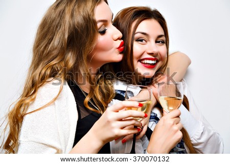 Close up funny portrait of pretty girls having fun on amazing party, bright make up, long hairs, holding glasses with champagne, pretty portrait of best friends, image with flash. - stock photo