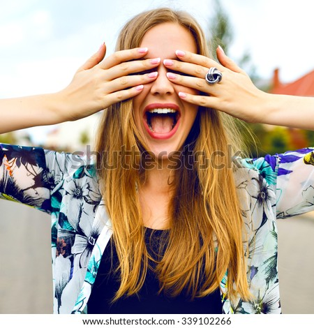 Close up funny portrait of smiling blonde girl close her eyes buy her hands, bright colors, positive emotions, cheerful youth concept. - stock photo