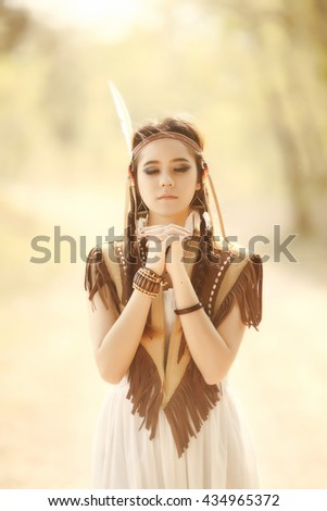 Close-up girl archer with traditional costume suit and fur hat. Summer forest on the background. Vintage tone. - stock photo