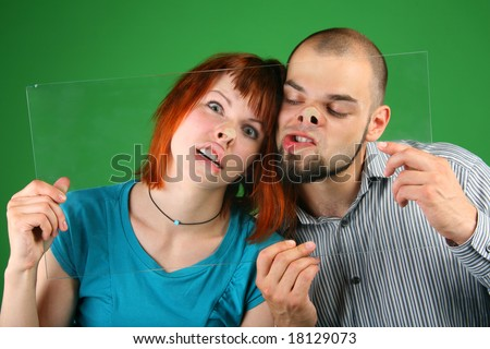 Close up girl with red hair and guy grimace behind glass