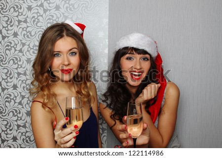 Close-up girlfriends hold champagne glasses at christmas party