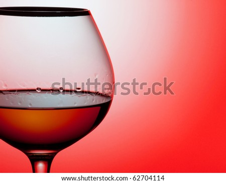 Close up glass of brandy on a red background