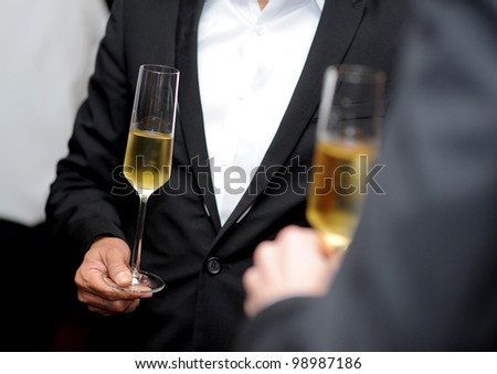 close up glasses of champagne in hand - stock photo