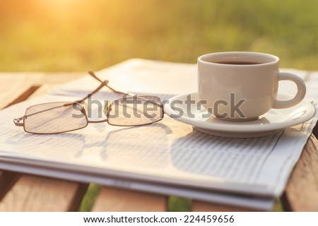 Close up glasses on newspaper and Coffee on the table in the morning - stock photo
