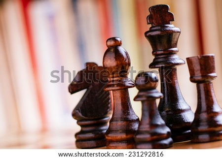 Close up Glossy Black Wooden Chess Pieces- King, Bishop, Knight, Rock and Pawn, Standing on Chess Board. - stock photo