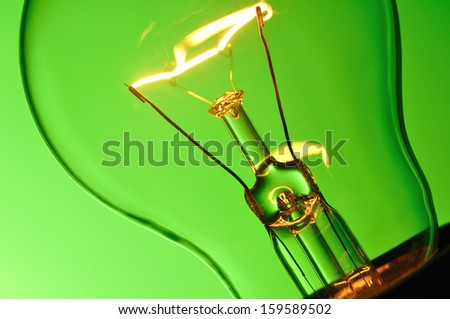 Close up glowing light bulb on green background  - stock photo