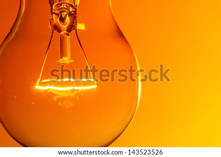 Close up glowing light bulb on orange background - stock photo