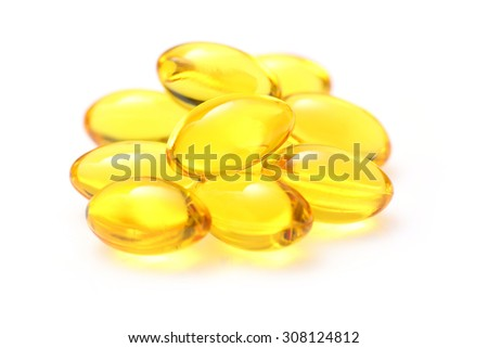 Close up golden color oil supplements in soft gel capsule, healthy product concept
