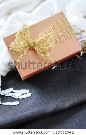 Close up golden gift box with white scarf background