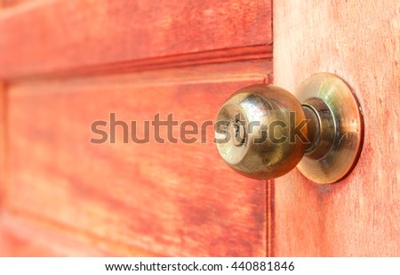Close up golden knob on red wooden door background