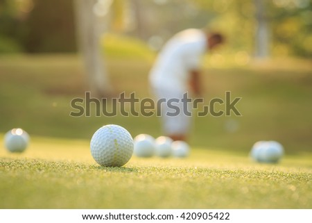 Close up golf ball and blurred of man playing golf in green course - stock photo