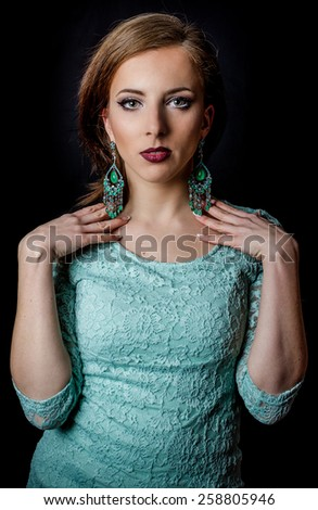 Close up Gorgeous Young Woman Posing in Elegant Mint Green Dress and Earrings with Both Hands on her Shoulders While Looking at the Camera, Isolated on Black Background. - stock photo