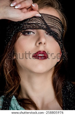 Close up Gorgeous Young Woman with Makeup, Pulling up the Black Net on her Face While Looking at the Camera Sensually, on a Black Background - stock photo