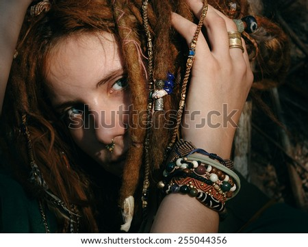 Close up Gorgeous Young Woman with Stylish Bracelets Touching her Hair While Looking at the Camera. - stock photo