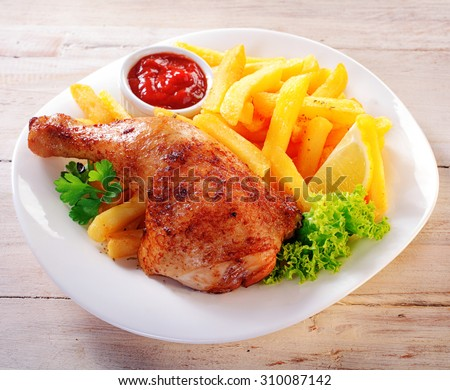 Close up Gourmet Appetizing Chicken and Fries Meal on a White Plate with Fresh Lettuce, Lemon Slice and Ketchup Sauce. - stock photo