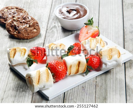 Close up Gourmet Grilled Strawberry and Marshmallow on Stick on top of White Board with Chocolate Dip and Cookies on the Side. Placed on Wooden Table. - stock photo