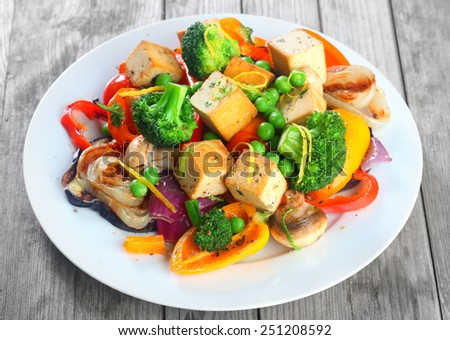 Close up Gourmet Healthy Main Dish on White Plate with Tofu, Broccoli, Mushrooms, Beans and Spices. Served on Wooden Table - stock photo