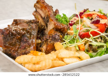 Close up Gourmet Main Dish with Grilled Pork Rib and Fried Potatoes on White Plate - stock photo