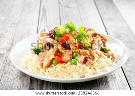 Close up Gourmet Meat Slices with Fresh Vegetables Above Rice, Placed on White Plate on Wooden Table. - stock photo