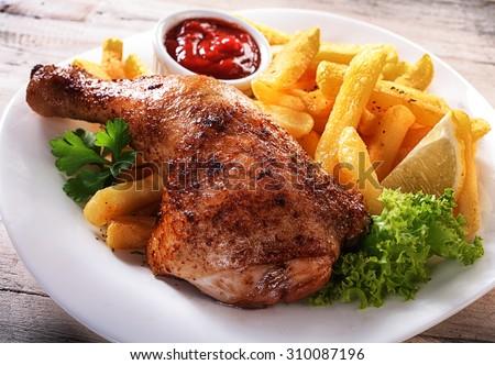 Close up Gourmet Tender Juicy Chicken and Fries Dish on a White Plate with Fresh Lettuce, Lemon and Sauce. - stock photo