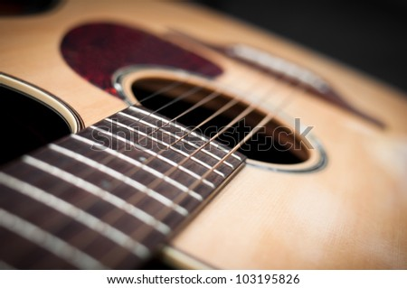 Close-up guitar body with sound hole and strings