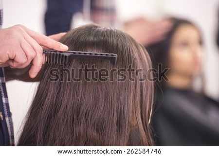 Close-up hairdresser combing hair for client hair in hairdressing salon. - stock photo