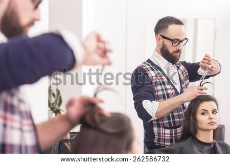 Close-up hairdresser cutting hair  for a beautiful brunette girl in hairdresser salon. - stock photo