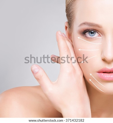 Close-up half face portrait of young, attractive woman with arrows on her face. Face lifting concept. - stock photo