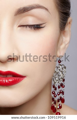 close-up half face portrait of young beautiful woman in ear-rings - stock photo