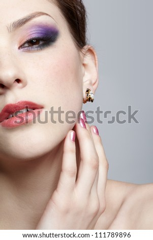 close-up half-face portrait of young beautiful woman touching her face with manicured fingers - stock photo