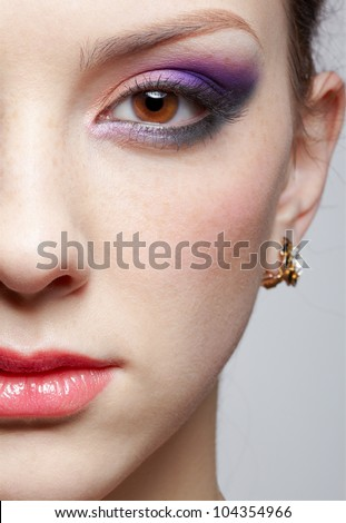 close-up half-face portrait of young beautiful woman with violet eye shadow - stock photo