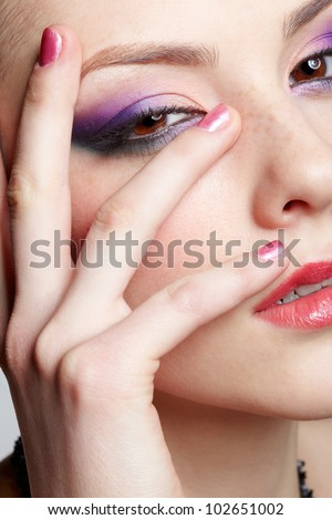 close-up half-face portrait of young beautiful woman with violet eye shadow and manicured fingers - stock photo