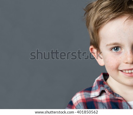 close up half portrait of an adorable red hair 5-year old child face with freckles smiling for childhood, copy space on grey background studio - stock photo