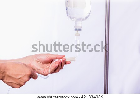 Close up hand adjustment saline IV drip for patient in hospital with copy space - stock photo