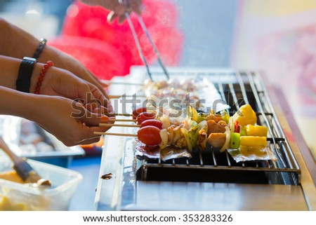 close up hand grilling pork barbecue on grill - stock photo