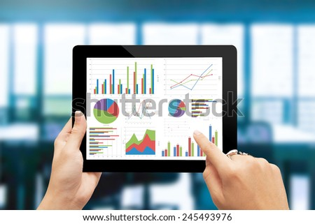 Close up hand holding digital tablet with analyzing graph - stock photo