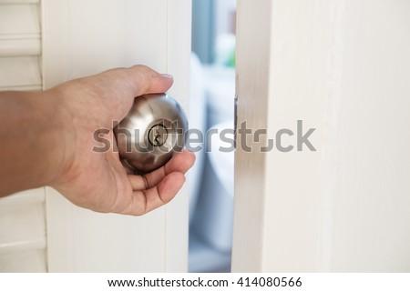 Close-up hand holding door knob, opening door slightly, selective focus - stock photo