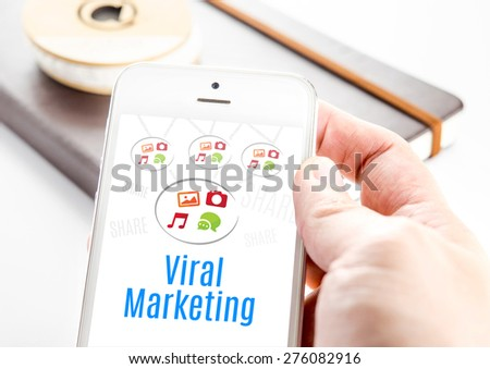 Close up hand holding smart phone with Viral marketing word and icons with notebook at background, Mobile technology concept - stock photo