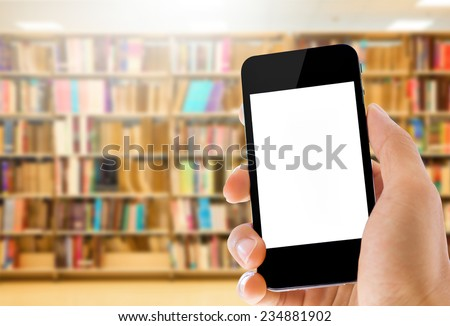 close up hand holding smartphone on library background  - stock photo