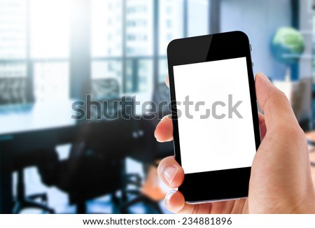 close up hand holding smartphone on office background - stock photo
