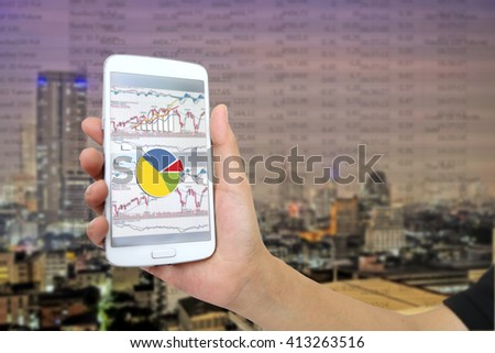 Close up Hand of Business girl to check stock by mobile phone with trench graphic chart  - stock photo