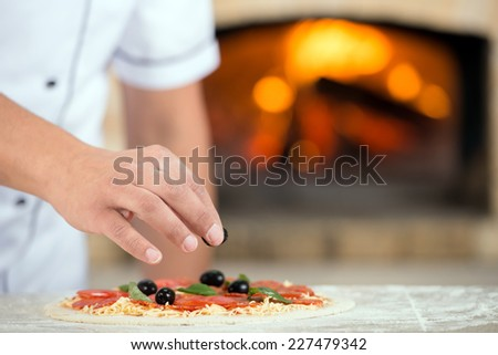 Close-up. Hand of chef baker in white uniform making pizza at the kitchen. - stock photo
