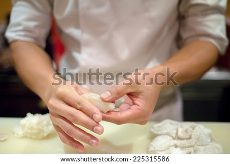 Close up hand of Japanese chef making sushi - stock photo