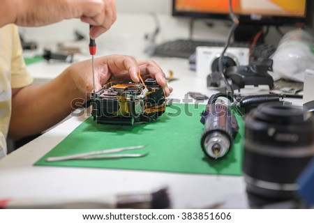 Close up hand of male technician repairing Camera - stock photo