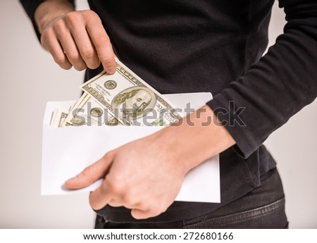 Close-up hand of man is holding envelope with money.