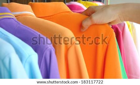 close up hand of woman choosing colorful polo shirt shopping at store - stock photo