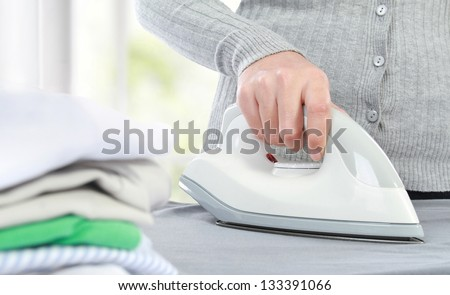 close up hand of woman ironing clothes on the table - stock photo