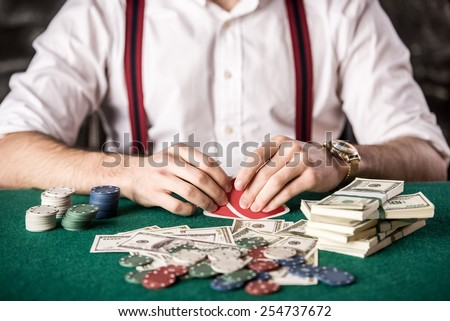 Close-up hand of young man, while playing poker game, with money and chips. - stock photo