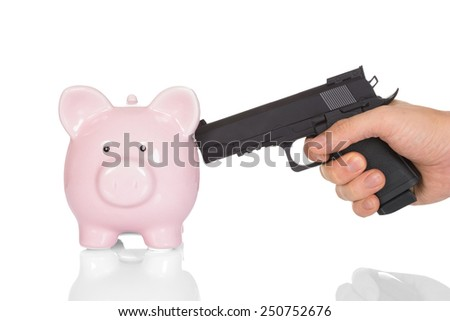 Close-up Hand Pointing Gun At A Piggy Bank Over White Background